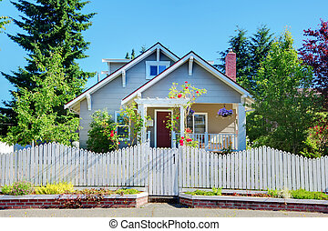 Grey small cute house with white fence and gates.