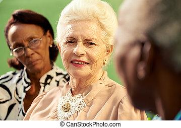 Group of elderly black and caucasian women talking in park