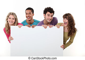 group of friends holding a blank poster