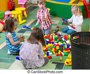 Group of kids playing with colorful constructor on floor