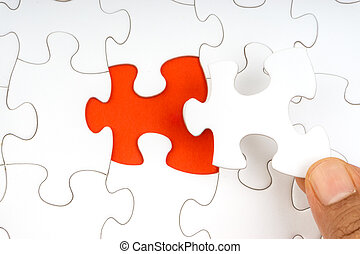 Hand put the last piece of jigsaw puzzle closeup