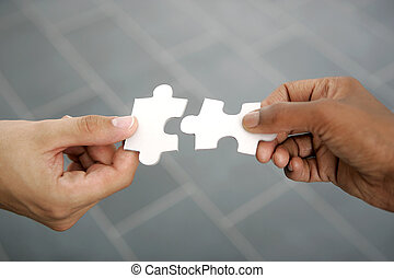 hands trying to fit two puzzle piec