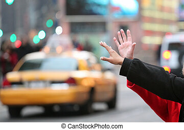 hands waving for a cab taxi in new york