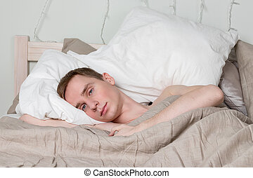 Handsome young adult man sleeping in bed. Sexy guy is resting