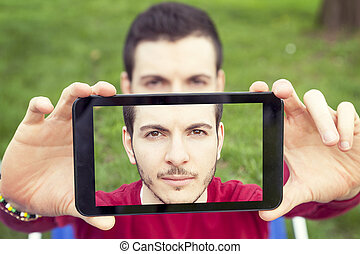 handsome young adult take a selfie with smart phone
