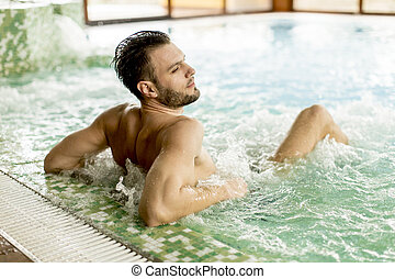 Handsome young man relaxing in hot tub