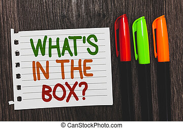 Handwriting text What s is In The Box question. Concept meaning Curiosity Opening a gift Surprise package Colorful words with white page red green orange pen on blackish wooden desk.
