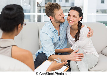 Happy couple reconciling at therapy session in therapists office