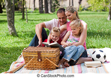Happy family reading in a park