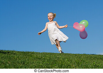 happy summer child running outdoors with balloons