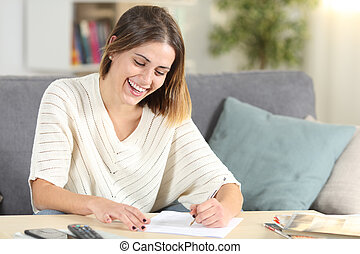Happy woman filling form on a couch at home