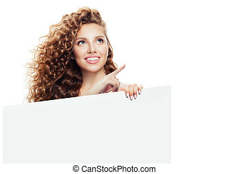 Happy woman pointing up and holding white empty paper board background isolated on white