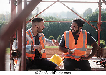 Happy Workers In Construction Site During Lunch Break