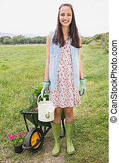 Happy young brunette gardening
