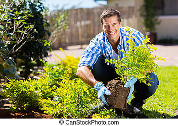 happy young man gardening in backyard
