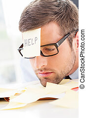 Help! Frustrated young man in formalwear with adhesive note on his forehead leaning his head at the table