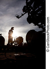 A silhouette of a high clearance sprayer being filled