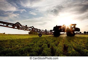 A silhouette of a high clearance sprayer on a field