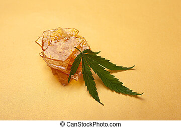 high thc, pieces of yellow cannabis wax and green leaf, marijuana concentrate