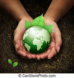 human hands holding green earth with a leaf on Fertilizer soil background