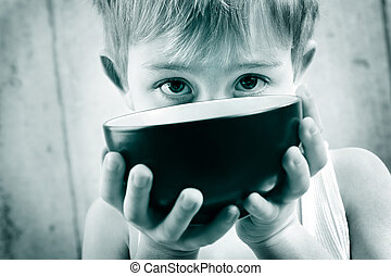 a young boy in monotone peeks over an empty rice bowl