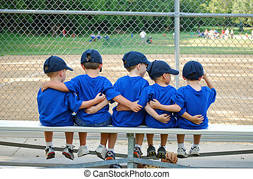five little boys put their arms around each other while waiting for their baseball game to start