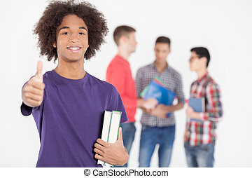 I love studying! Cheerful African teenage boy holding books and gesturing while his friends standing on background