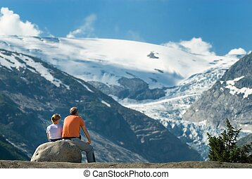 Senior couple taking a rest and day dreaming on a rock while watching an enormous glacial tongue
