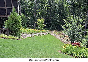 A landscaped yard with flowers and garden on a slopping lot.