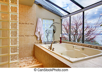 Large bath tub with window wall with water view.
