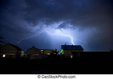 Lightning in the cloudy storm sky over village