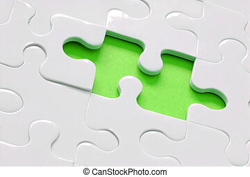 White jigsaw with piece missing and lime green background
