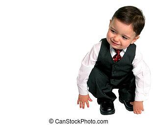 Toddler boy in 3 piece suit bends down to peek around the corner.