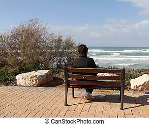 Loneliness. Woman sitting alone on a bench near winter sea