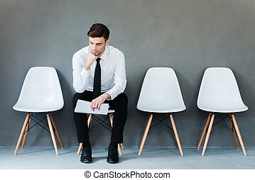 Long time of waiting. Pensive young businessman holding paper and holding hand on chin while sitting on chair against grey background