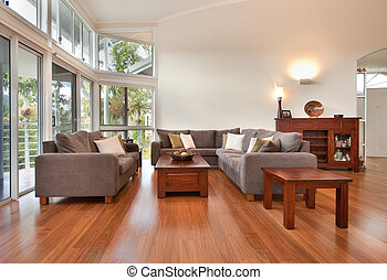 A beautiful modern lounge room with rich wooden floors, high ceilings, light brown lounge suite and rich dak wooden furniture