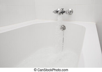 Luxury bath tub and faucet with water.
