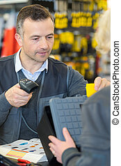 male sales clerk scanning item in hardware store