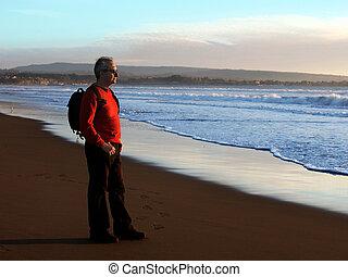 Man enjoying sunset by the ocean