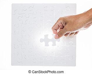 Man hand holding jigsaw puzzle piece