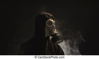 Smoke rising behind a man in a gas mask