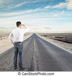 man standing on road looking to horizon
