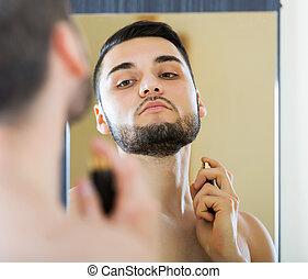 Man spraying fragrance perfume