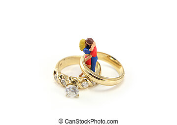 A miniature couple is hugging and kissing inside two wedding rings. They are against a white background. Could be used for a marriage or love concept.