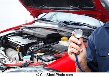 Mechanic with a stethoscope. Auto repair shop.