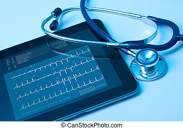 Doctor workplace with digital tablet and stethoscope. Electrocardiogram (ECG) on tablet screen. Application of modern technology in medicine concept.