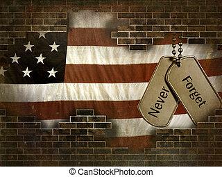 Military dog tags on American flag behind brick wall.