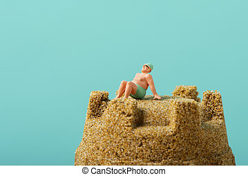 miniature man in swimsuit on the beach