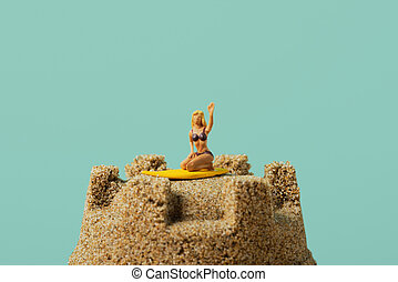 miniature woman on a sandcastle