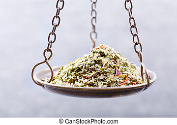 mixed dried green herbs in balance scale